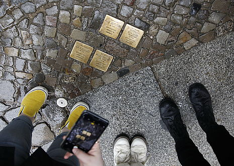 Participants taking pictures of Stolpersteine with cellphone.